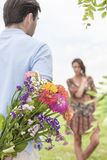 Rear view man surprising woman with bouquet in park Royalty Free Stock Photo