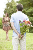 Rear view man surprising woman with flowers in park Stock Photos