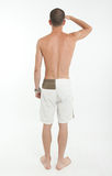 Rear view of man in swimming trunks looking far. Rear view of a young man wearing swimming trunks looking at the horizon Stock Photos