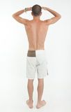 Rear view of man in swimming trunks looking far Stock Image