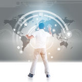 Person with global connections. Rear view of man touching social communication buttons on world map Stock Photo