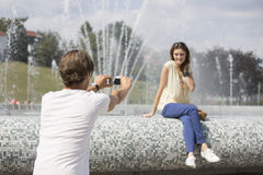 Rear view of man videotaping woman against fountain Stock Photos