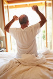 Rear View Of Man Waking Up In Bed In Morning Stock Photo