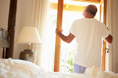Rear View Of Man Waking Up In Bed In Morning Stock Images