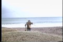 Rear view of man walking down beach with fishing rods