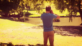 Rear view of man walking and taking photo with retro camera stock video footage
