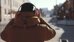 Rear view, man wear headphones outdoors, video included original audio. Rear view, anonymous man wear headphones outdoors, video included original audio stock video