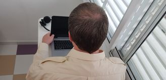 Rear view of a man wearing official collar shirt sitting near window royalty free stock photography