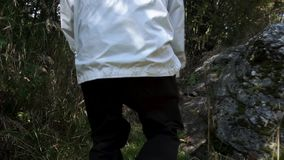 Rear view of a man in white jacket walking in tall grass on the forest background, slow motion. Footage. Adult forester