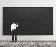 Rear view of the man who is going to write something on the black chalkboard. Wooden floor and concrete wall. A concept of the beg Royalty Free Stock Photography