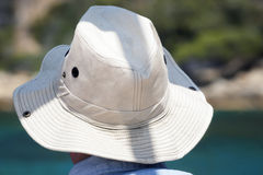 Rear view of  man or woman in sun hat. Rear view of young man or woman in white sun hat on sandy beach background Stock Photos