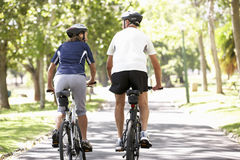 Rear View Of Mature Couple Cycling Through Park Royalty Free Stock Image