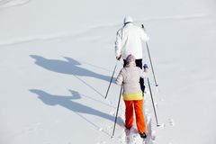 Backs of skiers. Rear view of mature couple skiing in winter park stock photography