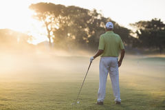Rear view of mature golf player. Standing on field Stock Photography