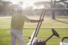 Rear view of mature man standing by golf buggy Stock Photography