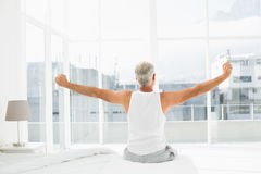 Rear view of a mature man stretching arms in bed Royalty Free Stock Image