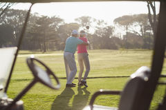 Rear view of mature man teaching woman to play golf royalty free stock images