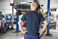 Rear view mechanic looking at car Stock Image