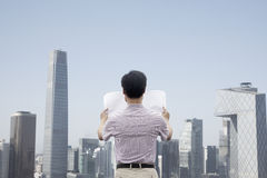Rear view of mid adult man in front of cityscape holding newspaper Stock Photography