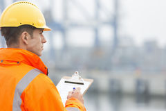 Rear view of mid adult man writing on clipboard in shipping yard Stock Photos