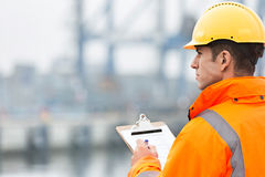Rear view of mid adult man writing on clipboard in shipping yard Stock Image