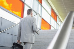Rear view of middle aged businessman walking up stairs in railroad station Royalty Free Stock Photography