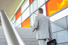 Rear view of middle aged businessman walking up stairs in railroad station Royalty Free Stock Photo