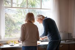 Rear view at middle-aged couple preparing breakfast together in royalty free stock photo