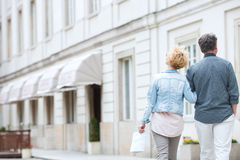 Rear view of middle-aged couple walking by building Royalty Free Stock Image