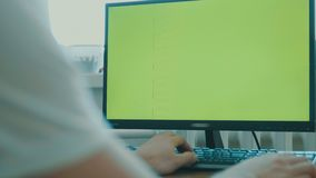 Rear view of a middle-aged man sitting in front of a large screen monitor. Green screen. Keyboard. Rear view of a middle-aged man sitting in front of a large stock footage