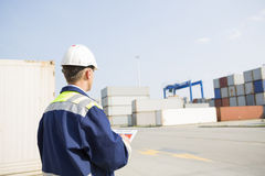 Rear view of middle-aged worker with clipboard in shipping yard Royalty Free Stock Photo