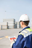 Rear view of middle-aged worker with clipboard in shipping yard Stock Image