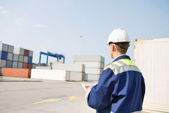 Rear view of middle-aged worker with clipboard in shipping yard Royalty Free Stock Images