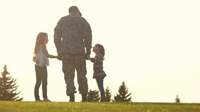 Rear view military man in camoubackgrounde with kids. stock footage