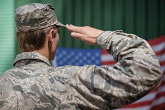 Rear view of military soldier giving salute to american flag. In boot camp stock photo