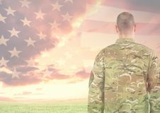 Rear view of military standing against american flag. Digital composite of Rear view of military standing against american flag Royalty Free Stock Image