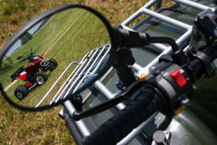 Rear view mirror. Red quad bike in rear view mirror Stock Image