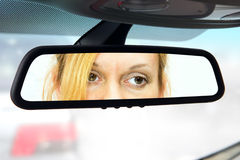 Rear-view mirror. Woman sits on driver's seat and Looks in the rear-view mirror Stock Photos