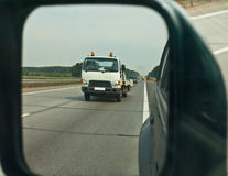Rear-view mirror. Tow-car in rear view mirror stock image