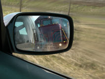 Rear View Mirror. Train in the background in mirror royalty free stock photo