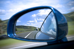 Rear view mirror. Reflecting road and sky stock image