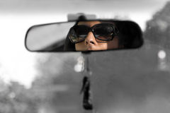 Rear View Mirror. The face of a young woman driving as seen in the rear view mirror in isolated color Stock Images