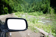 The rear-view mirror. In a car as a background Royalty Free Stock Images