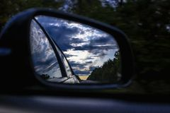 Rear view mirror of the car and dark sky. Rear view mirror of the car Royalty Free Stock Photography
