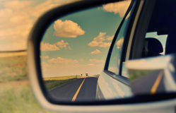 Rear view mirror and long road ahead Royalty Free Stock Image