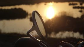 The Rear View Mirror of Motorcycle at Sunset. Beautiful Action Near Lake.