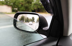 Rear-view mirror in rainy weather Royalty Free Stock Photo
