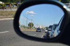 Rear view mirror. With a line of cars on a city street royalty free stock photo