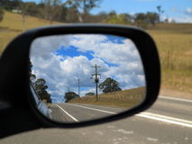 Rear view mirror reflecting landscape. The Australian countryside reflected in an exterior rear view mirror (at left-hand traffic&#x29 Royalty Free Stock Photography