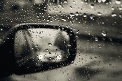 Rear view mirror seen through rain drops on the car window. Focus is on some water drops. Toned effect Royalty Free Stock Image